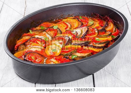 traditional French casserole - ratatouille: stewed zucchini red bell pepper parsley yellow squash eggplant tomato sauce and garlic in baking dish close-up