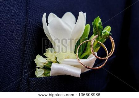 the groom's beautiful boutonniere with wedding rings.