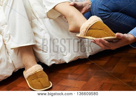 Hands of a caregiver helping feet of senior woman putting on slippers at home
