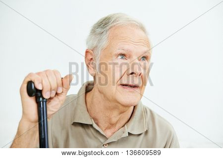Old man with can looking pensive into the distance