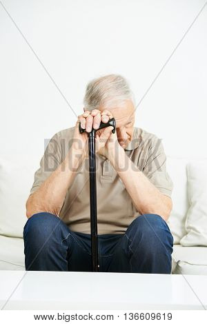 Sad senior man with cane sitting on a sofa