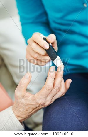 Blood glucose monitoring for old woman on her finger