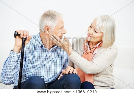 Old woman caressing check of senior man with cane