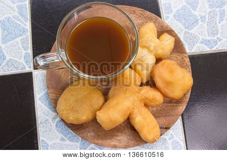 deep fried dough stick on the wooden tray with hot coffee