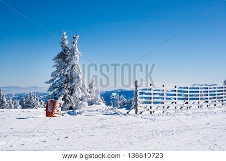 Vacation rural winter background with  white pines, fence, snow field, mountains, blue sky, copyspace