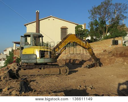 Excavator with hydraulic hammer in residential building site in Alora Andalusia