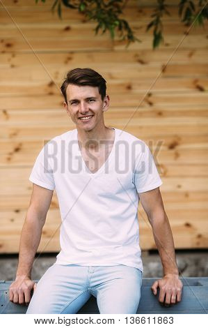 young handsome guy in shirt and jeans on the background of wooden wall