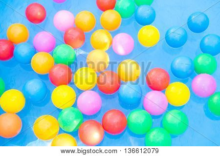 Colored balls floating in kiddie pool - red, pink, yellow, green, blue