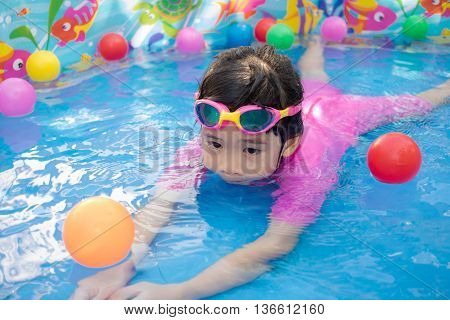 A baby girl in pink suit playing water and balls in blue kiddie pool