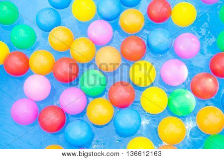 Colored balls floating in kiddie pool - yellow, blue, green, red, pink.