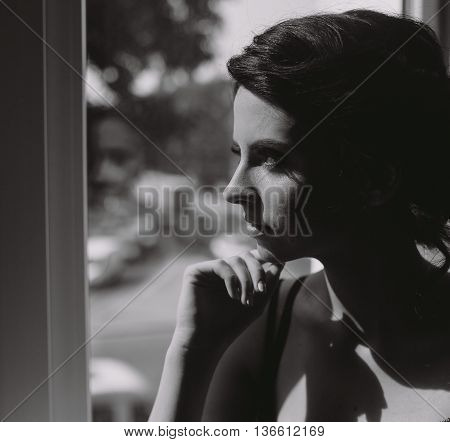 Bride in the morning sitting on the windowsill