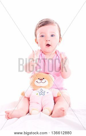 Baby girl clap her hands on white background.