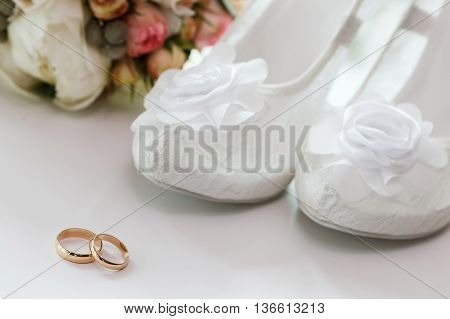Wedding rings and beautiful white bride's shoes