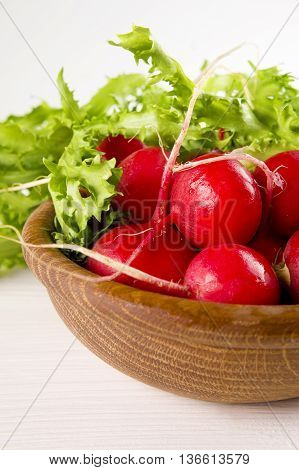 red radish and Fresh green lettuce in a wooden bowl