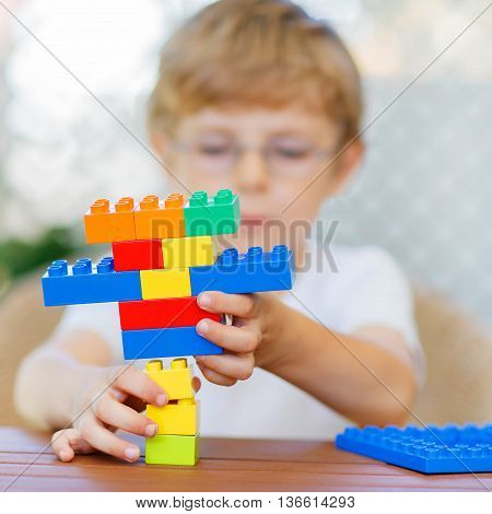 Little child with glasses playing with lots of colorful plastic blocks indoor. kid boy having fun with building and creating. Selective focus on multicolored toy