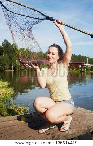 Smiling woman holds caught carp in landing net at pond bank.