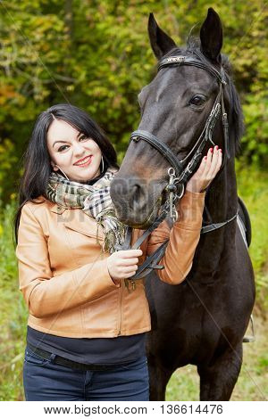 Smiling black-haired woman stands with horse in park.