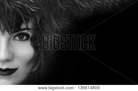 Close-up portrait of mysterious young beautiful woman with black feather headdress on black background with copy space. Model fashion shooting. Smoky eyes make-up. Sensual lips. Perfect pure skin. Femme fatale. Retro style. Vintage style. Cabaret girl. Bl
