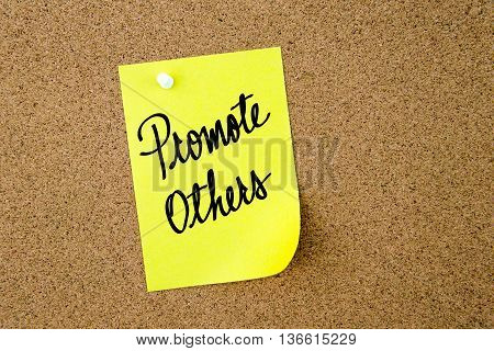 Promote Others Written On Yellow Paper Note