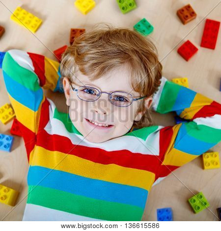 Adorable little blond child with glasses playing with lots of colorful plastic blocks indoor. Happy Kid boy wearing colorful shirt and having fun with building and creating.