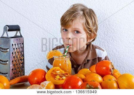 Cute little preschool kid boy drinking fresh healthy organic smoothie. Healthy meal and drink. Orange fruits and vegetables.