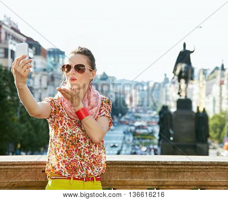 Happy Young Woman Blowing Air Kiss And Taking Selfie In Prague