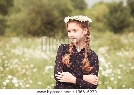 Smiling teenage girl posing in meadow with camomile wreath outdoors. Looking away. Summer portrait. Teenager hood.