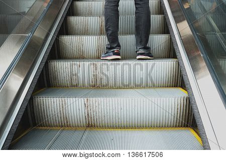 Black jeans and gray shoes going upstair by escalator