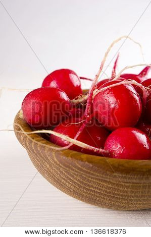 Red radish in a wooden bowl on a white background.