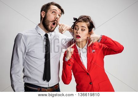 The funny business man and woman communicating with imaginary phones on a gray background.