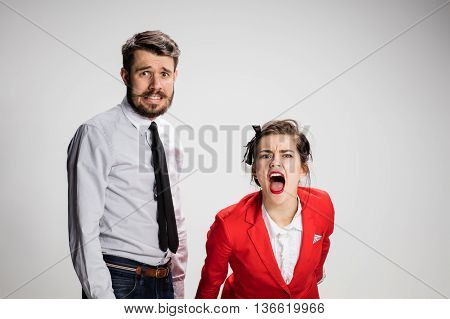 The business man and screaming woman on a gray background