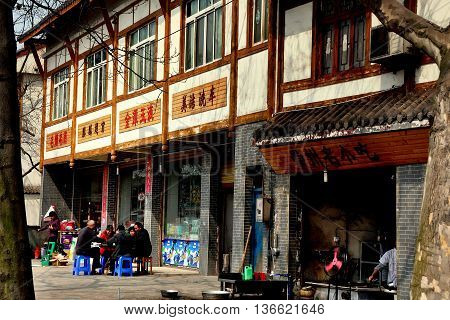 Long Feng China - March 5 2013: Group of people seated on plastic chairs playing cards outside in front of a wooden half-timbered house on the town's main street