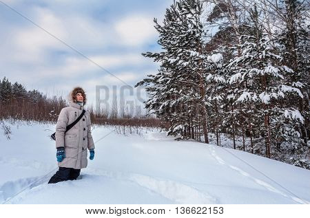 Girl standing in the winter forest and looking at the tree
