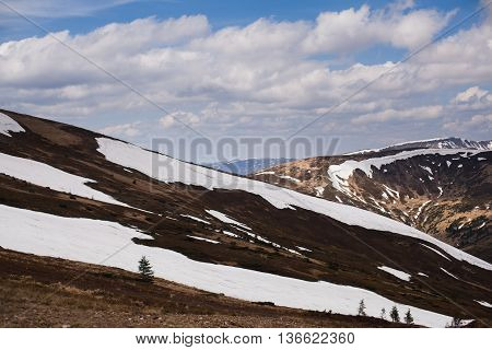 mountain on the clouds with snow in spring