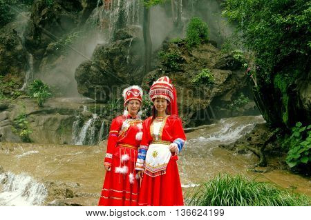 Guilin China - April 20 2006: Two Chinese women dressed in traditional Yao people clothing standing by a waterfall in Seven Stars Hill Park