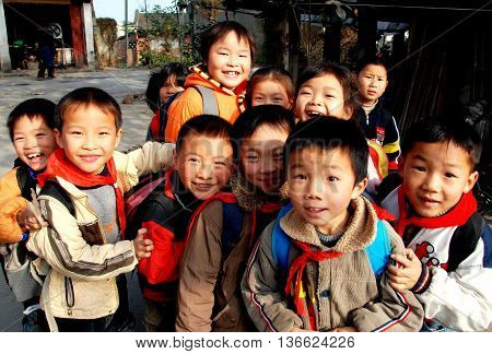 Li'an Village China - November 26 2007: A group of smiling Chinese children wearing their red school scares gather outside their school