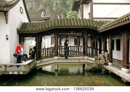 Guilin China - April 20 2006: The Qi Xia Temple with bridge spaning a pool filled with goldfish at Seven Stars Hill Park