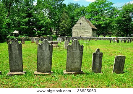 \Ephrata Pennsylvania - June 6 2015: Gravestones in God's Acre Burial Ground and the Weaver's House at historic 18th century Ephrata Cloister *