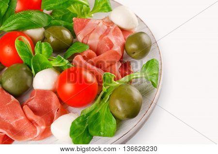 Italian appetizer: prosciutto mozzarella cherry tomatoes lettuce and olives