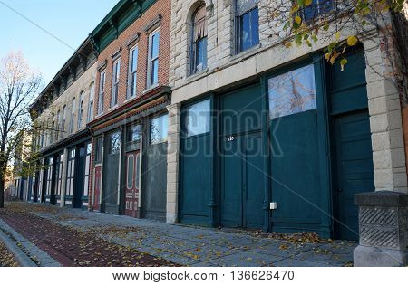 JOLIET, ILLINOIS / UNITED STATES - NOVEMBER 1, 2015: Boarded up storefronts line the sidewalk in downtown Joliet, Illinois.