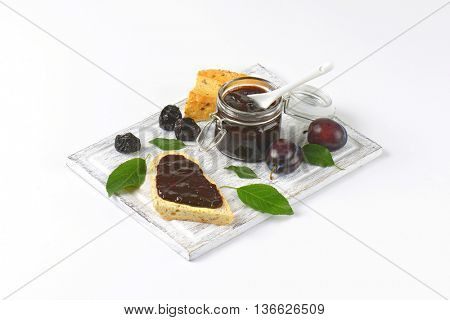 plum jam on a piece of baguette and in a jar, fresh plums and prunes on cutting board