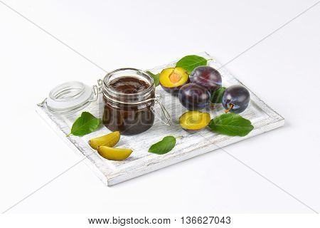 jar of plum jam and fresh plums on wooden cutting board