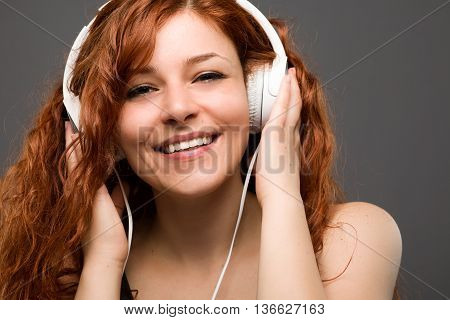 Smiling Redhead Woman Listening to Music with Headphones