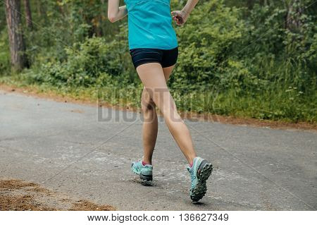 feet girl running down road in woods during a marathon