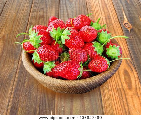 bowl with strawberries on a wooden background.