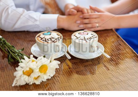 Cups of coffee with words I love you. Close up of hands of young couple sitting at the table and holding them together while drinking coffee in the cafe