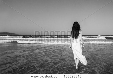 Young beautiful woman brunette with long dark hair and gold bracelets in white dress entering the Indian Ocean at sunset. Romantic style. Fashion model shot. Romance. Bohemian boho chic. Hippie style. Dreaming. Black and white image.