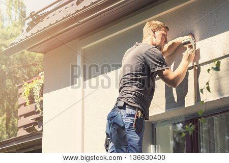 young electrician installing lamp on house facade