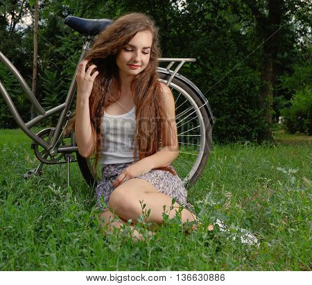 Beautiful smiling girl sitting next to bike on fresh grass with her eyes half closed toned image
