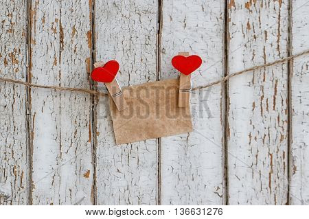 Note on the background of an old fence with clothespins in a heart shape